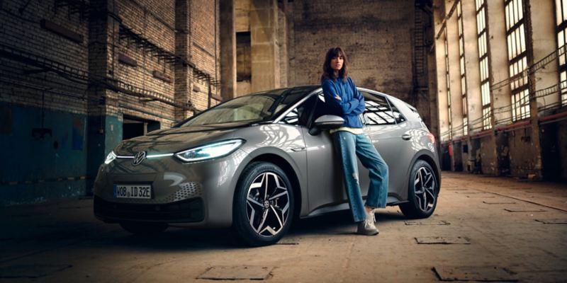 Chica apoyada en un Volkswagen ID.3 gris aparcado en una fábrica con los faros encendidos