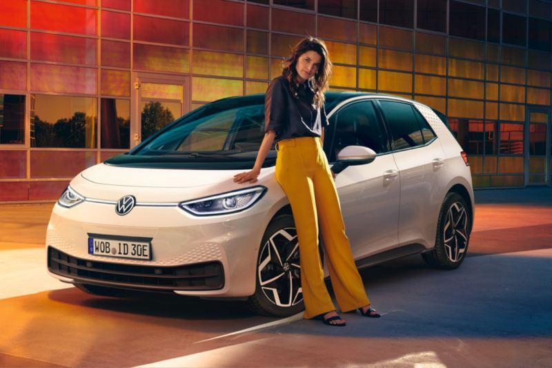 Chica apoyada junto a un Nuevo Volkswagen ID.3 blanco aparcado en la calle