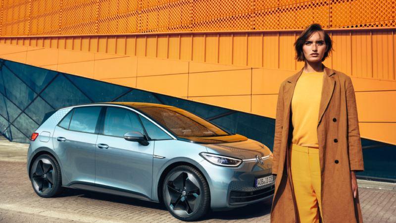 Mujer joven vestida de naranja delante de un Volkswagen ID.3 aparcado en la calle