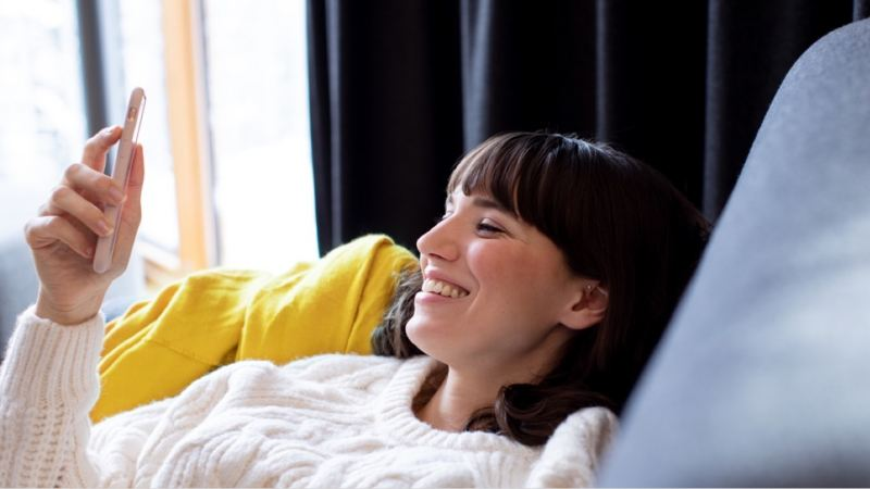 Chica tumbada en un sofá gris sonriendo mientras mira su móvil