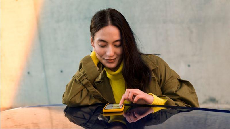 Chica mirando su teléfono móvil sobre el techo de un Volkswagen ID.3