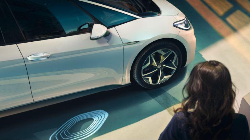 Mujer junto a un Volkswagen ID.3 blanco emitiendo una luz holográfica en el suelo