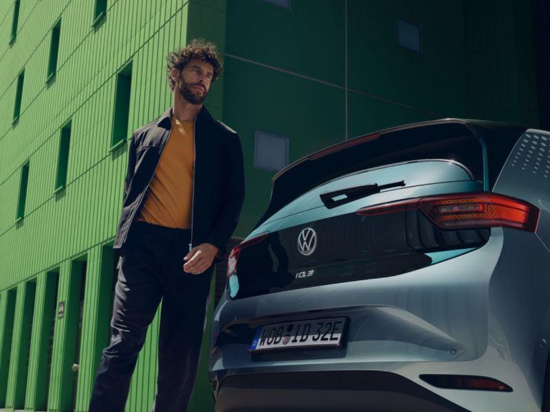 Hombre andando tras un Nuevo Volkswagen ID.3 gris aparcado en la calle