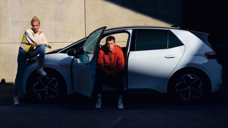 Chicos mirando a la cámara posando junto a un Nuevo Volkswagen ID.3 blanco