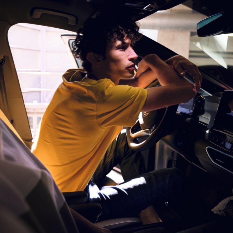 Chico con una camiseta amarilla apoyado en el volante de un ID.3 con la puerta abierta