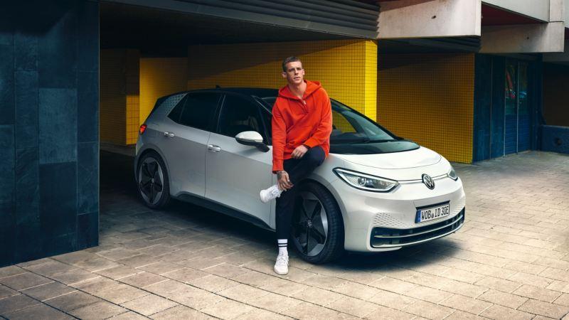 Chico joven con una sudadera roja apoyado sobre el capó de un Volkswagen ID.3 blanco aparcado en un porche