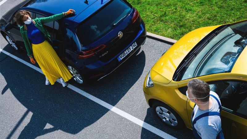 Mecánico de Volkswagen y chica joven con mascarillas junto a dos vehículos de Volkswagen aparcados en a la calle