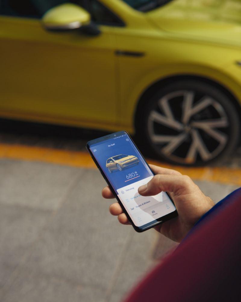 Mano con un móvil utilizando la aplicación We Connect frente a un Golf 8 amarillo