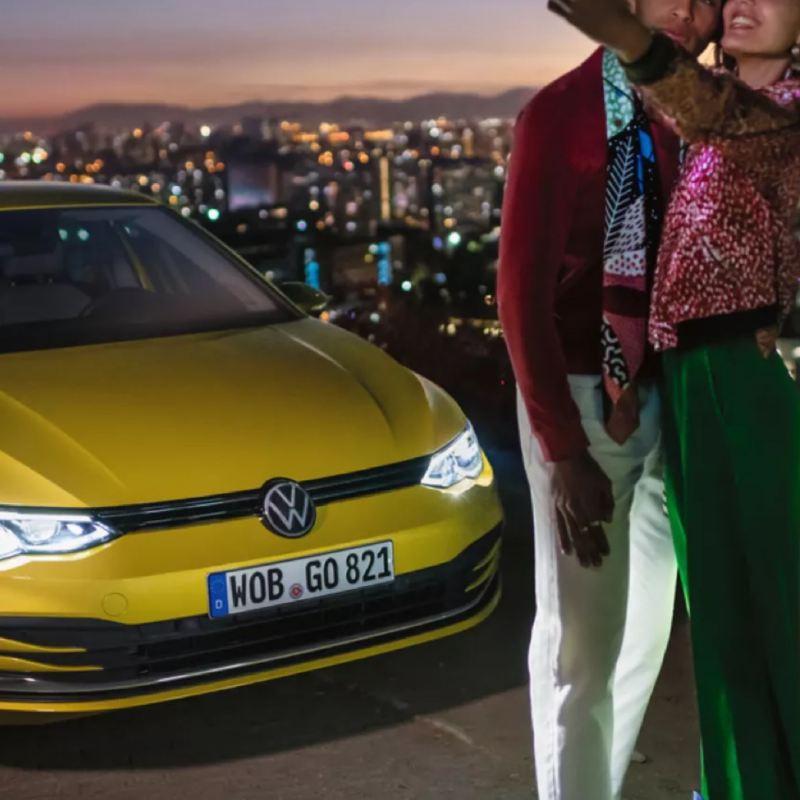 Una pareja haciéndose un selfie junto a un Volkswagen Golf 8 amarillo aparcado con la ciudad de fondo