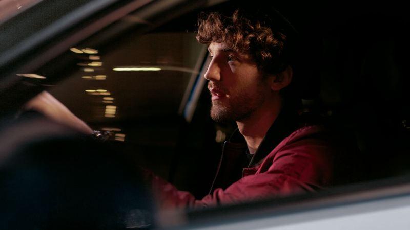 Chico joven conduciendo un T-Roc blanco en la noche