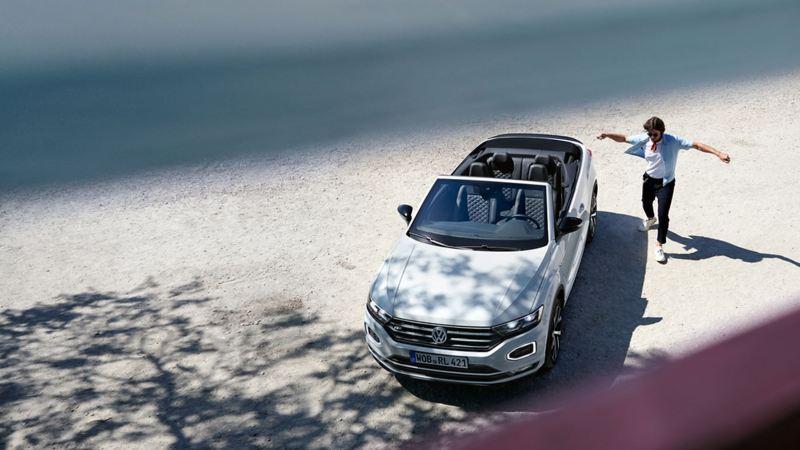 Volkswagen T-Roc Cabrio blanco visto desde arriba aparcado en un exterior con un hombre joven a su lado