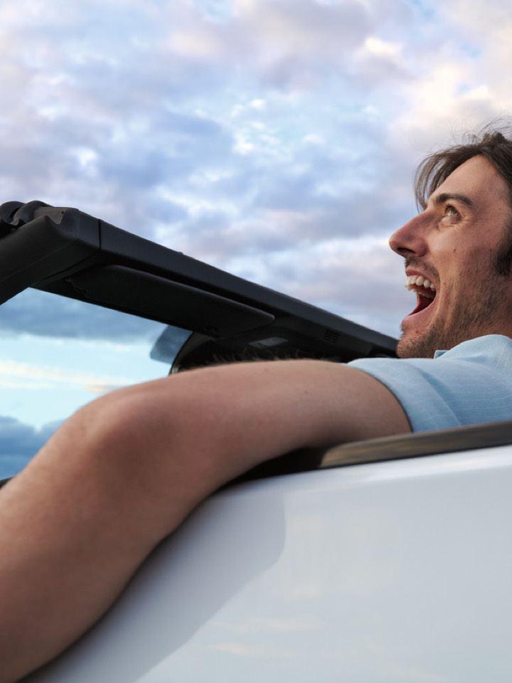 Vista de lado de un hombre sonriendo conduciendo un Volkswagen T-Roc Cabrio blanco