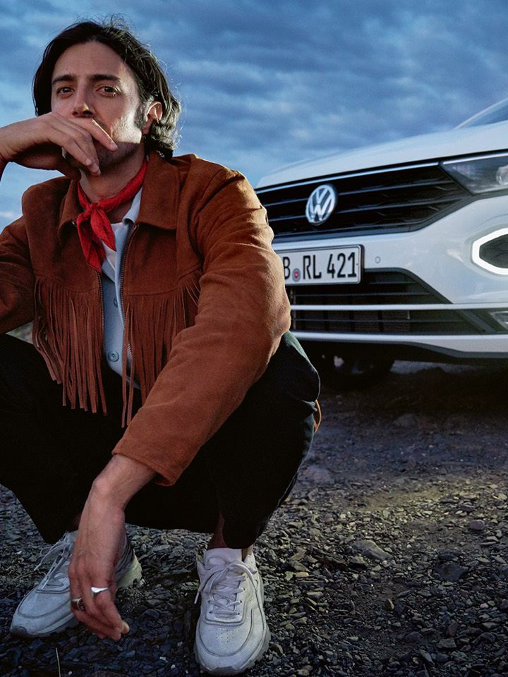 Hombre agachado mirando al frente delante de Volkswagen T-Roc Cabrio blanco