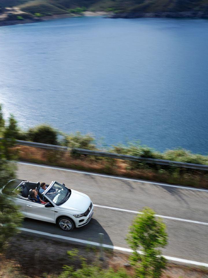 Volkswagen T-Roc Cabrio blanco visto desde arriba circulando por una carretera junto a un pantano