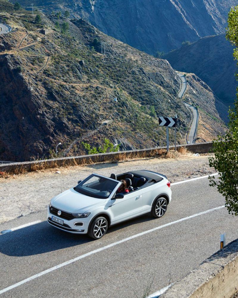 T-Roc Cabrio blanco con la capota bajada avanzando por una carretera en la montaña