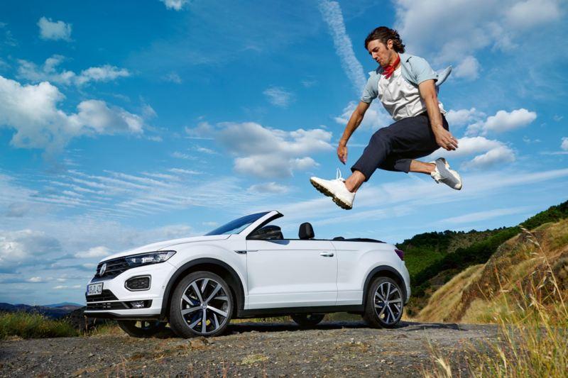 Hombre saltando delante de un Volkswagen T-Roc Cabrio blanco en el campo con la capota abierta