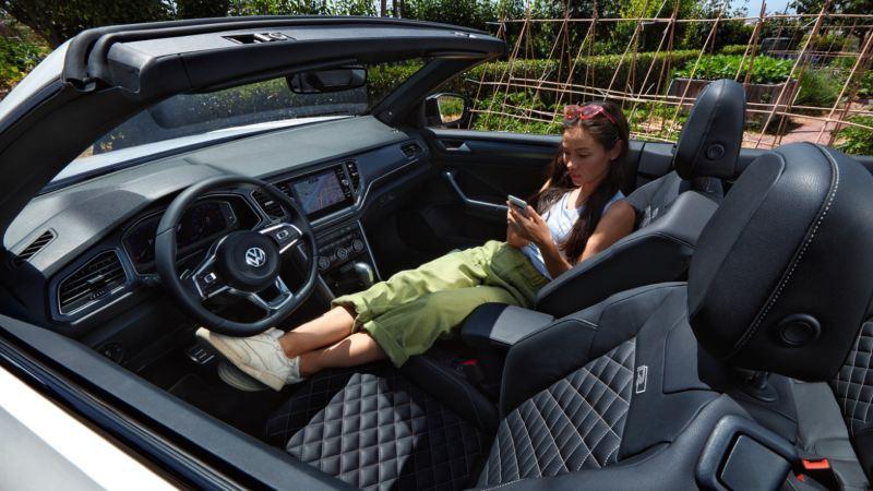 Mujer recostada en los asientos delanteros de un T-Roc Cabrio blanco con la capota abierta