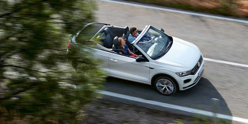 Una pareja en el Nuevo T-Roc Cabrio blanco con la capota abierta por una carretera