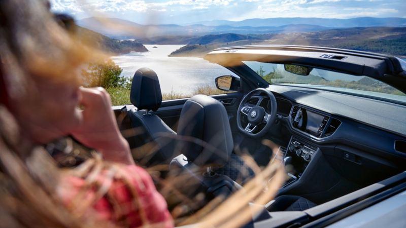 Interior de un T-Roc Cabrio aparcado en un parking con una chica delante