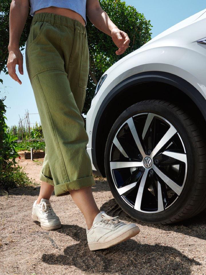 Detalle de la llanta de un Volkswagen T-Roc Cabrio blanco y las piernas de una mujer caminando delante