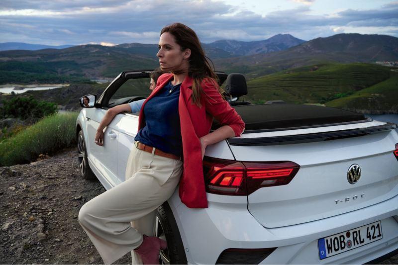 Mujer apoyada en un Volkswagen T-Roc Cabrio blanco con la capota abierta