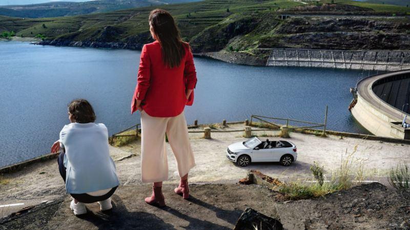 Pareja joven de espaldas mirando un pantano desde lo alto y un Volkswagen T-Roc Cabrio blanco