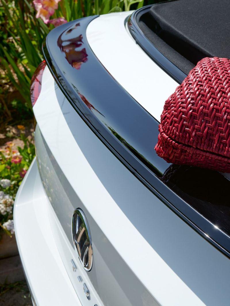 Bolso rojo sobre el capó de un T-Roc Cabrio blanco aparcado en la naturaleza