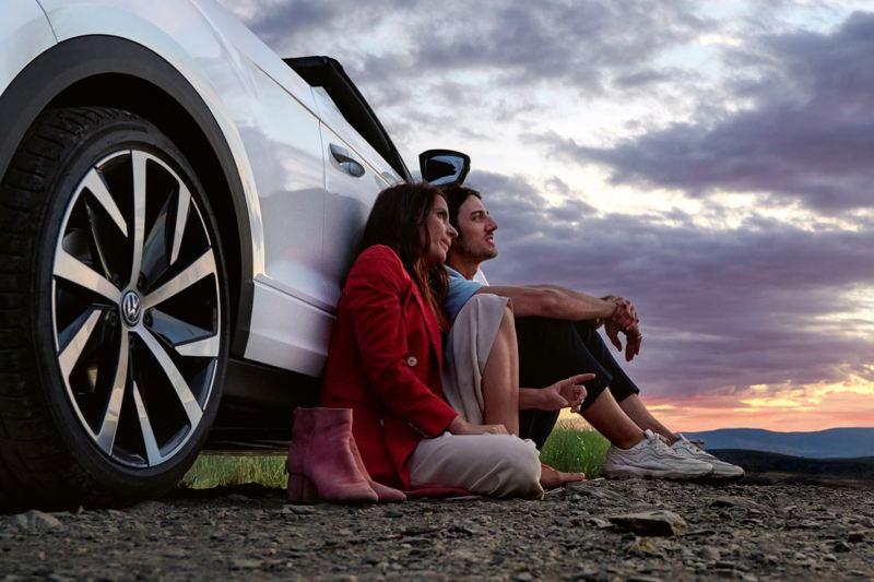 Pareja joven sentados en el suelo apoyados en un T-Roc Cabrio blanco