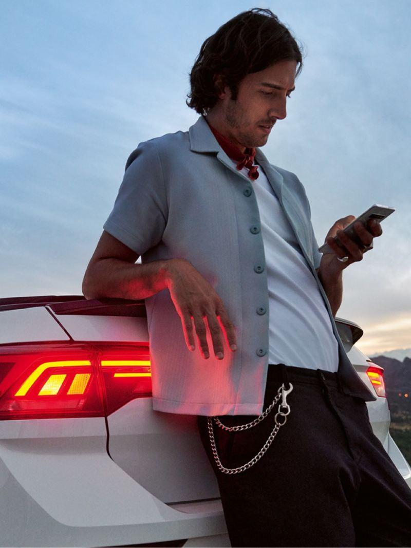 Chico apoyado en el capó de un T-Roc Cabrio blanco con las luces traseras encendidas