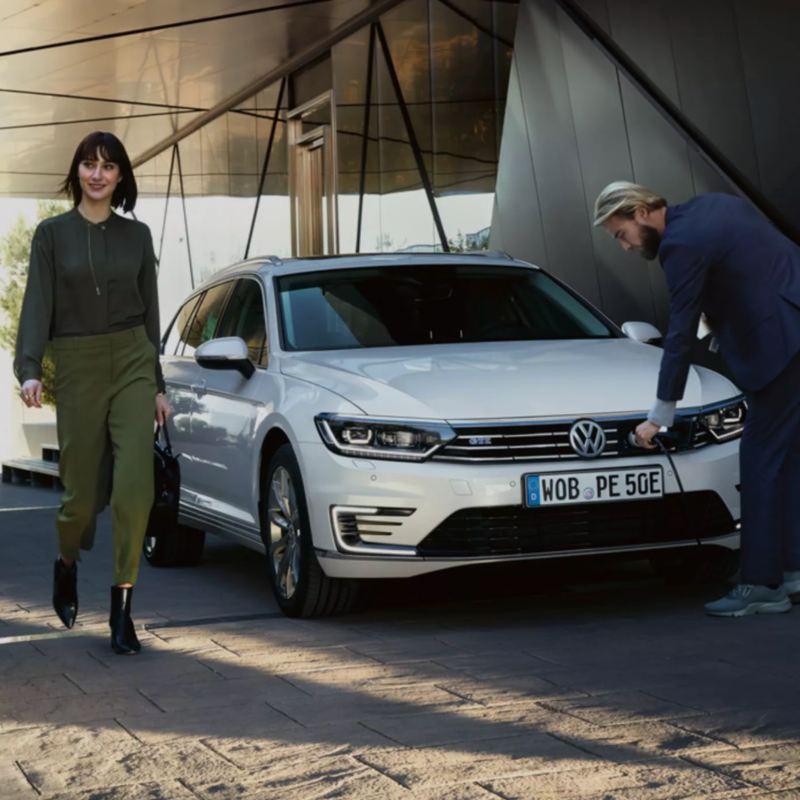 Pareja junto a un Volkswagen Passat blanco conectado a un cargador eléctrico