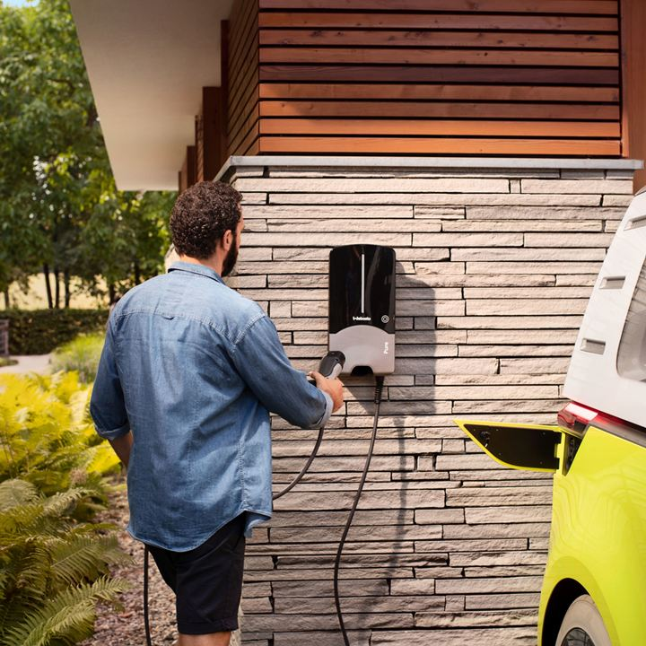Hombre frente a una casa dejando el enchufe en el soporte de carga de un ID.Buzz
