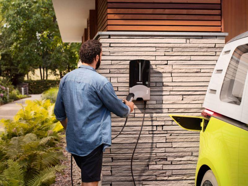 Hombre cogiendo el enchufe de un cargador Wallbox en la fachada de una casa junto a un ID.Buzz