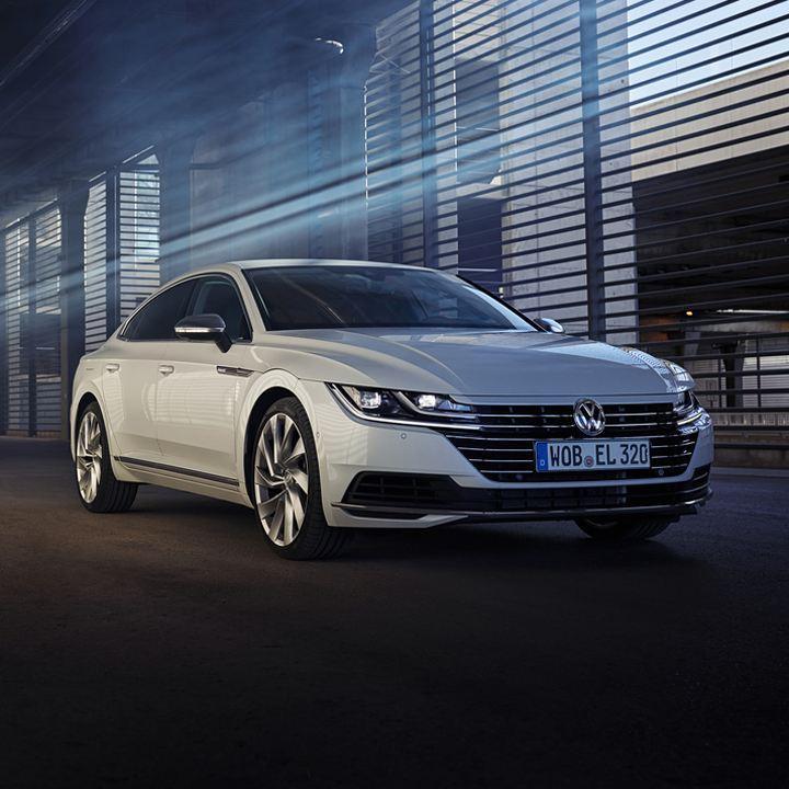 Volkswagen Arteon blanco circulando por la ciudad de noche