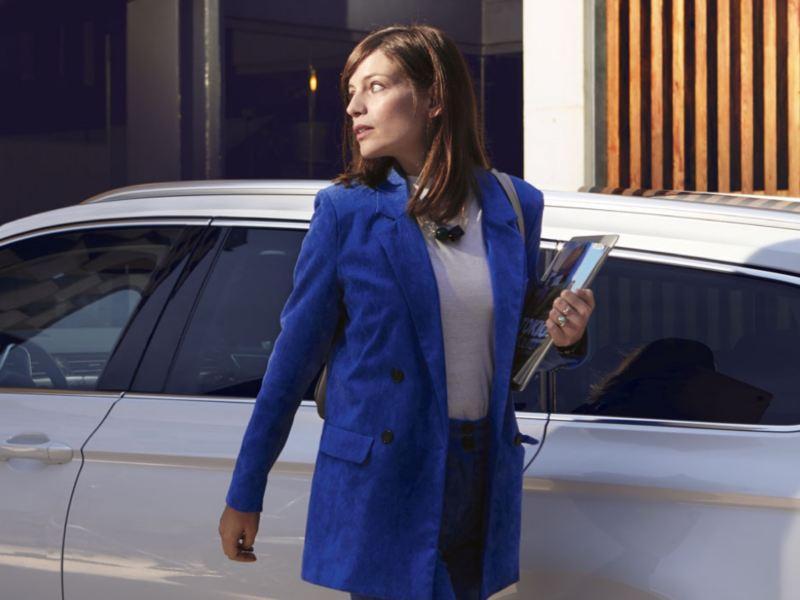 Mujer vestida de azul caminando delante de un Volskwagen