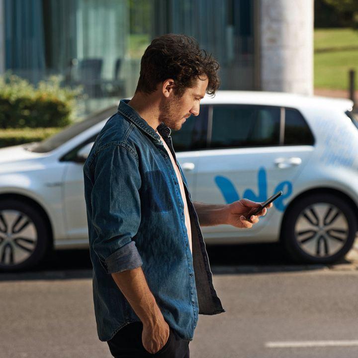 Hombre joven consultando un móvil delante de un Golf blanco aparcado con el logo de Volkswagen We