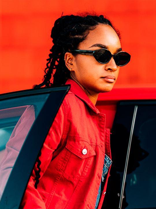 Chica con unas gafas de sol y una chaqueta roja saliendo de un T-Cross rojo