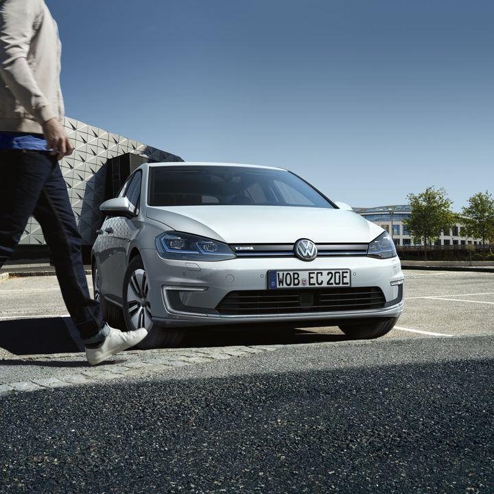 Hombre caminando delante de un Volkswagen e-Golf blanco