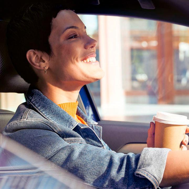 Mujer sonriente conduciendo un Volkswagen mientras sujeta un café