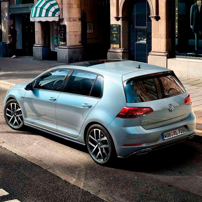 Vista trasera de un Volkswagen Golf plateado aparcado en la acera de una calle