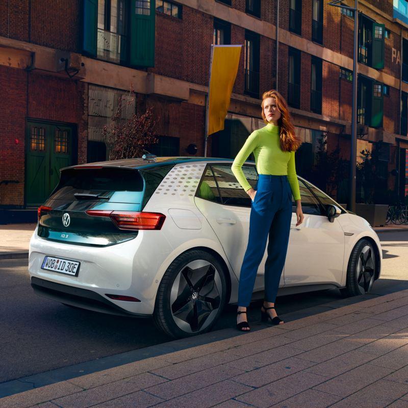 Chica con un jersey verde de espaldas a un ID.3 blanco aparcado en la calle