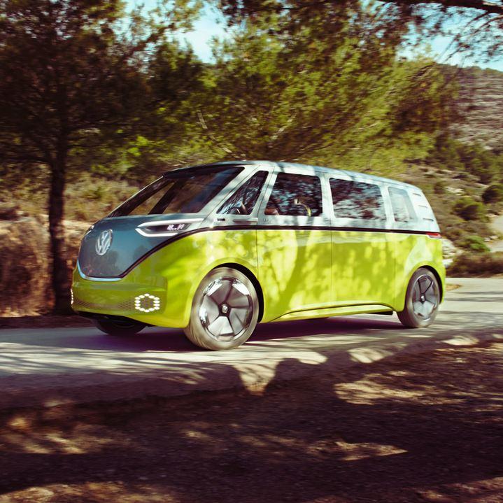 Volkswagen ID. Buzz amarilla circulando por una carretera en un bosque de pinos