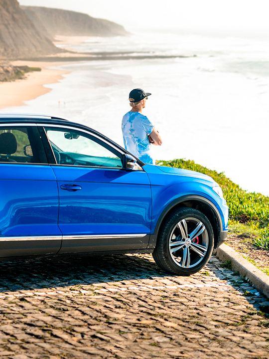 Hombre joven apoyado en el capó de un Volkswagen SUV azul mirando el mar