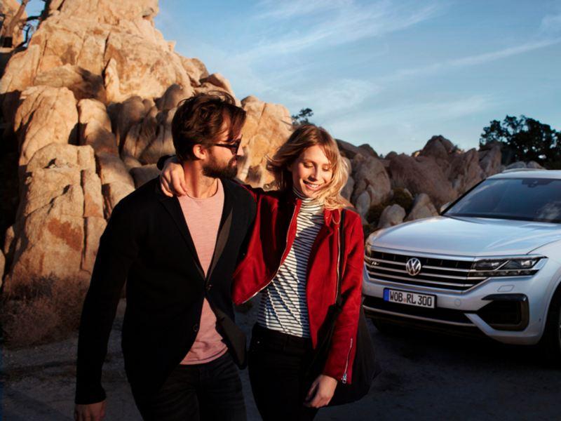 Pareja cogidos del brazo frente a unas rocas mientras dejan atrás un Volkswagen Touareg blanco