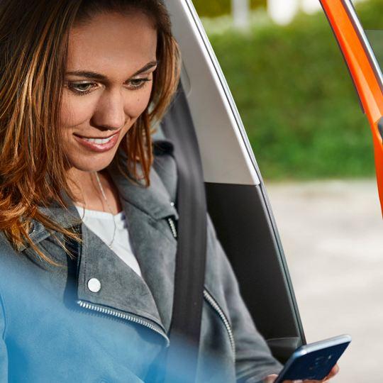 Mujer joven sonriendo sentada en un Volkswagen con un móvil en las manos
