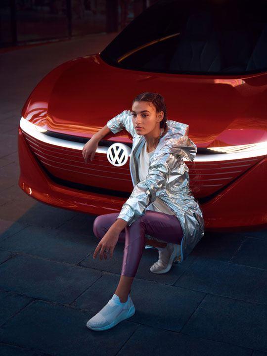 Chica en cuclillas con un abrigo plateado apoyada en el frontal de un ID.Vizzion