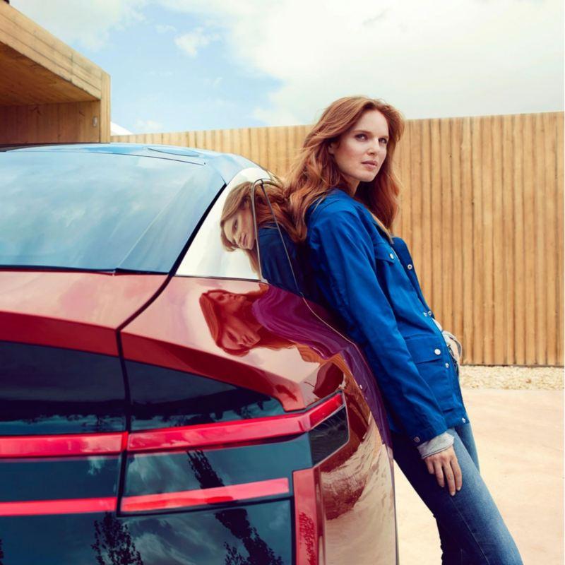 Chica de azul apoyada en un Volkswagen ID. Crozz visto parcialmente desde atrás