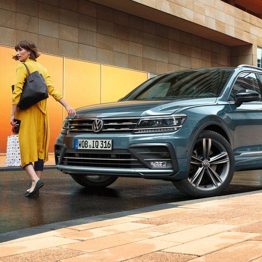 Mujer caminando delante de un Volkswagen Tiguan Allspace