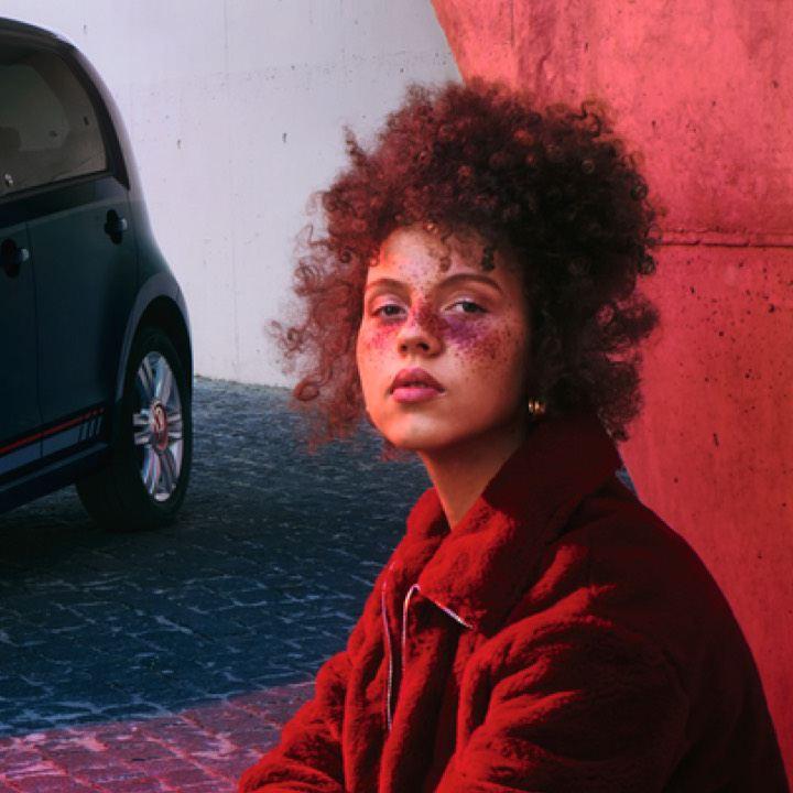 Chica joven con mirada seria y una iluminación roja frente a un Volkswagen up!