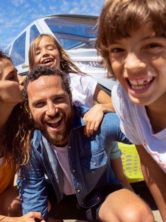 Familia sonriente de cerca mirando directamente a la cámara frente a un ID.Buzz