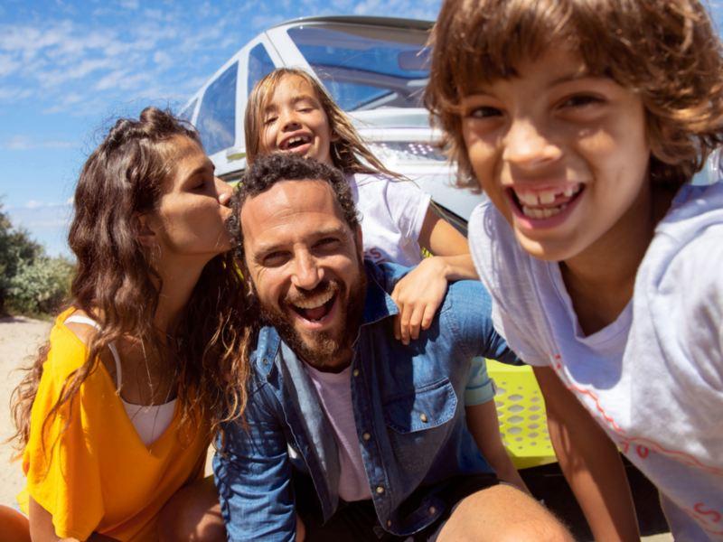 Familia sonriendo al aire libre delante de un furgón Volkswagen